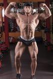 Un homme est engagé dans le bodybuilding dans le gymnase, soulève la barre et forme ses muscles images libres de droits