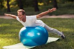 Un homme est engagé dans un parc de yoga avec une boule bleue de yoga Il se trouve sur la boule répandant ses mains Image libre de droits