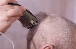 Un homme est les cheveux coupés sur sa tête La coiffure de l'homme dans le salon de coiffure photos stock