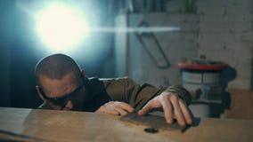 Un homme est traitement de la billette en bois sur une surface de travail en bois avec une machine de meulage banque de vidéos