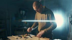 Un homme est traitement de la billette en bois sur une surface de travail en bois avec une machine de meulage clips vidéos