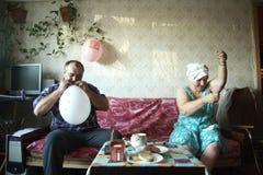 Un homme et ballons d'un inflat de femme Photographie stock