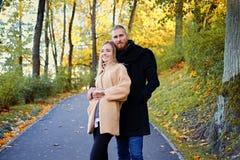 Un homme et son amie posant sur la route en automne se garent Photo stock