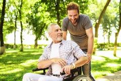 Un homme et son père plus âgé marchent en parc Un homme porte son père dans un fauteuil roulant Images libres de droits