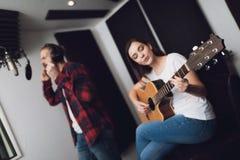 Un homme et une femme chantent une chanson à un studio d'enregistrement images stock