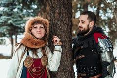 Un homme et une femme dans des costumes historiques se tiennent près d'un arbre photo stock