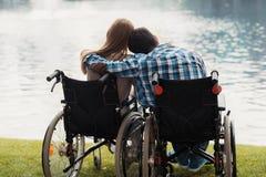 Un homme et une femme dans des fauteuils roulants s'asseyent sur le rivage de lac Ils se reposent s'étreignant Images stock