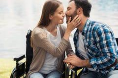 Un homme et une femme dans des fauteuils roulants s'asseyent sur le rivage de lac Une femme veut embrasser un homme Photo libre de droits