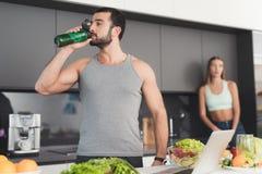 Un homme et une femme dans la cuisine pendant le matin Un homme boit un cocktail végétal Image libre de droits