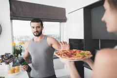 Un homme et une femme dans la cuisine pendant le matin Un homme boit un cocktail végétal et refuse la pizza proposée Photos stock