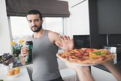 Un homme et une femme dans la cuisine pendant le matin Un homme boit un cocktail végétal et refuse la pizza proposée Images libres de droits