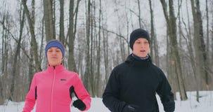 Un homme et une femme dans une veste rose pendant l'hiver fonctionnant par le parc dans le mouvement lent Style de vie sain banque de vidéos