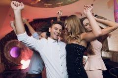 Un homme et une femme dansent dans le premier plan Derrière eux ils dansent et chantent leurs amis photos libres de droits