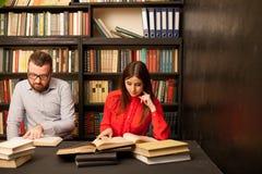 Un homme et une femme ont lu des livres dans la bibliothèque se préparent à l'examen images libres de droits