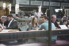 Un homme et une femme s'asseyent à travers entre eux dans un café i Photographie stock libre de droits