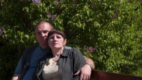 Un homme et une femme s'asseyent s'étreignant banque de vidéos