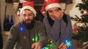 Un homme et une femme s'asseyent près de l'arbre de nouvelle année et des cadeaux de capture qui sont jetés à eux Les couples heu banque de vidéos