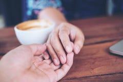 Un homme et une femme se tenant mains avec amour de sentiment Image libre de droits