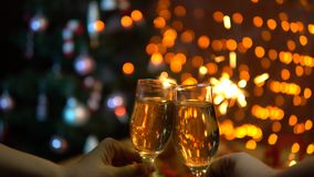 Un homme et une femme soulèvent des verres de champagne de scintillement au-dessus d'une table de fête banque de vidéos