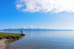 Un homme et une fille près de lac Sayram en ciel bleu Photo stock