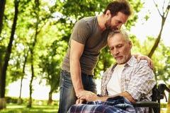 Un homme et un vieil homme dans un fauteuil roulant en parc L'homme a couvert le vieil homme de couverture Photographie stock libre de droits