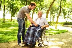 Un homme et un vieil homme dans un fauteuil roulant en parc L'homme a couvert le vieil homme de couverture Images libres de droits