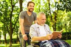 Un homme et un vieil homme dans un fauteuil roulant en parc L'homme a couvert le vieil homme de couverture Photo libre de droits