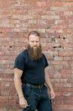 Un homme, un Européen avec une barbe, tient demi un tour sur le fond d'un mur rouge de kerf photos libres de droits