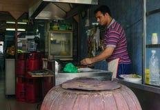 Un homme faisant cuire au restaurant local Image stock
