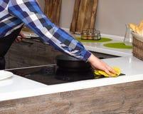 Un homme faisant le nettoyage dans la cuisine, le plan rapproché, la main et le chiffon modernes image stock