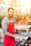 Un homme fait cuire des légumes sur le gril Photo libre de droits