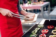 Un homme fait cuire des saucisses sur le gril à une partie des amis Photographie stock libre de droits