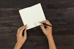 Un homme fait des notes dans un carnet Photographie stock libre de droits