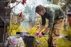 Un homme fait frire des chiches-kebabs sur Mongal dans son complot de jardin images stock