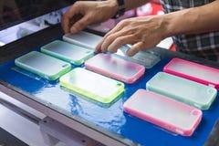 Un homme fait la caisse de smartphone pour la machine d'impression Innovation de couverture et de conception mobiles photo libre de droits