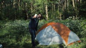 Un homme fait un appel visuel au téléphone Supports voisins une tente dans la forêt, début de la matinée banque de vidéos
