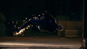 Un homme fait une secousse dans le ciel, tours des arts martiaux dans la ville de nuit, au ralenti clips vidéos