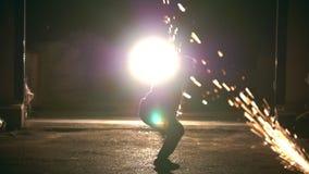 Un homme fait une secousse dans le ciel, tours des arts martiaux dans la ville de nuit, au ralenti banque de vidéos