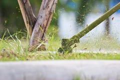 Un homme fauchant l'herbe Images libres de droits