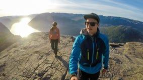 Un homme filmant lui et son amie tout en marchant sur la roche c?l?bre de Preikestolen en Norv?ge image stock