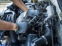 Un homme fixent de vieux moteurs de voiture Photo stock