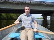 Un homme flottant sur un bateau monte avec photographie stock