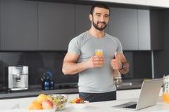 Un homme folâtre pose dans la cuisine Il tient un verre de jus et montre son pouce  Photographie stock libre de droits