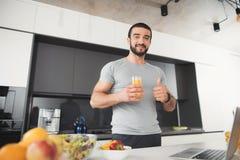 Un homme folâtre pose dans la cuisine Il tient un verre de jus et montre son pouce  Image stock