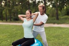 Un homme forme une femme faisant des exercices tout en se reposant sur une boule pour le yoga en parc Image stock