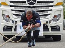 Un homme fort tire un grand camion Image stock