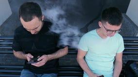 Un homme fumant un vape, un autre homme est tracassé par la fumée banque de vidéos