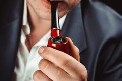 Un homme fume un tuyau photos stock