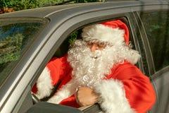 Un homme habillé comme Santa Claus livre des cadeaux sur la voiture Problèmes d'effort et de route images stock