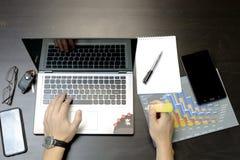 Un homme imprime sur un ordinateur portable, se trouvant à côté du téléphone, glasse de comprimé images libres de droits